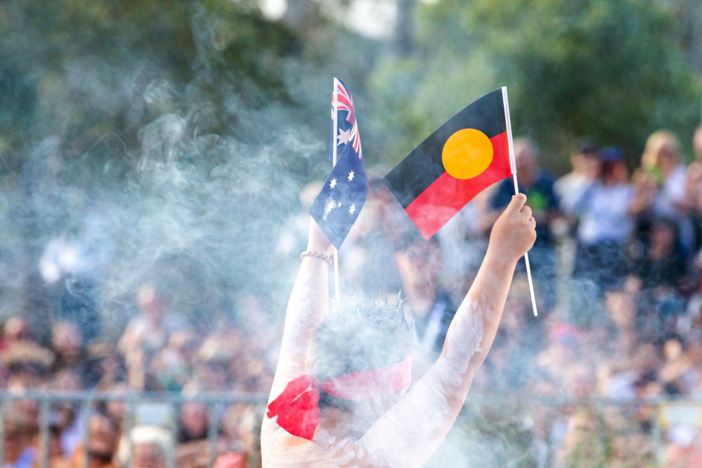 A First Nations person holding up the Australian and Aboriginal flag