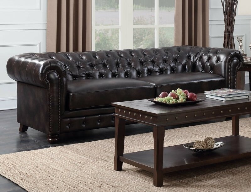 A black faux leather sofa with rolled arms and nailhead trim
