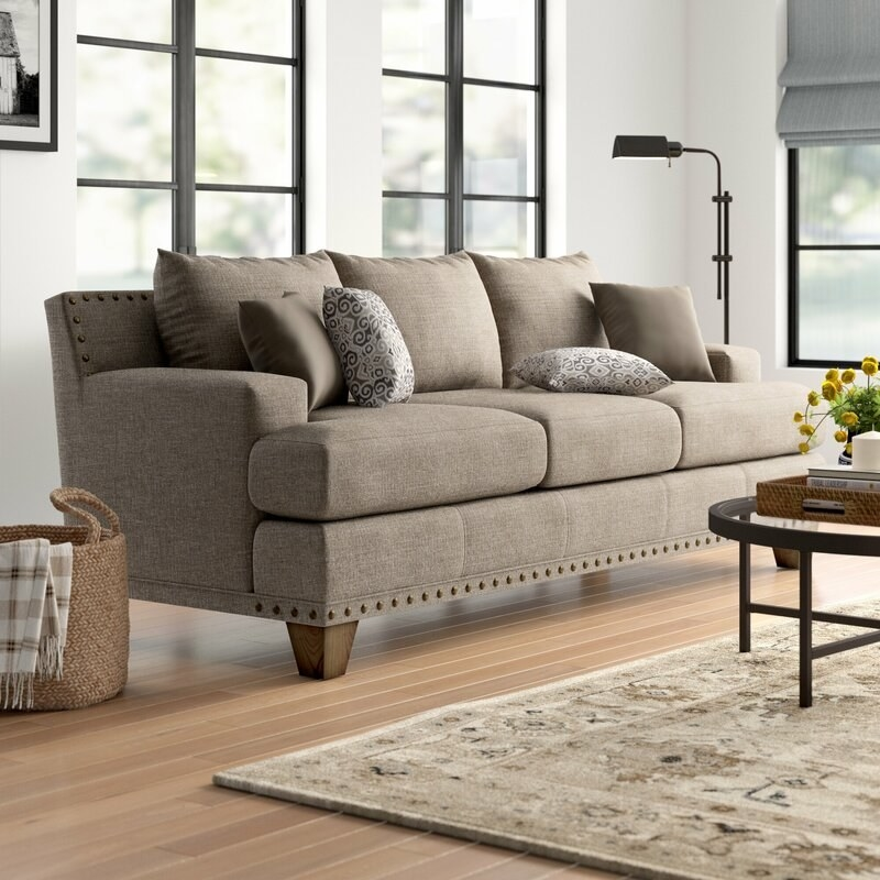The sandstone/beige sofa with low wooden legs and throw pillows included