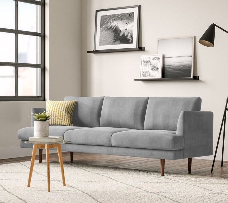 The light gray couch with skinny arms and wooden legs