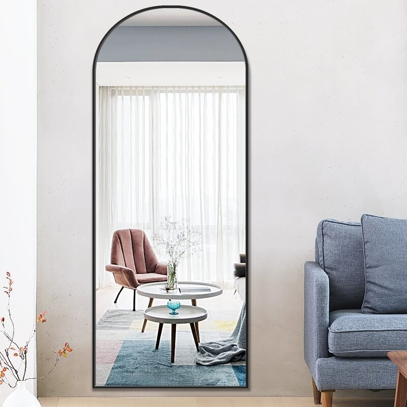 A full-length mirror with a black, arched frame