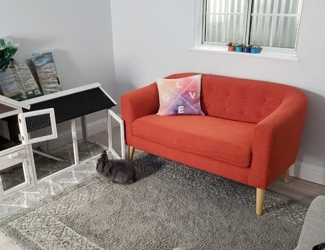 The bright orange loveseat with wooden legs