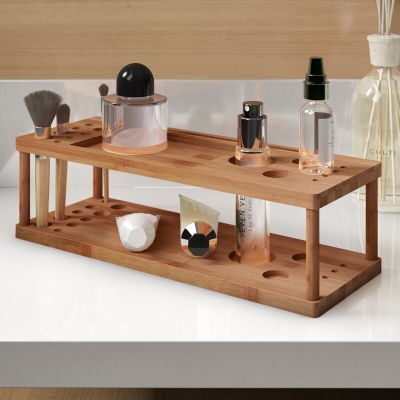 A freestanding bamboo makeup organizer with two shelves and a variety of differently sized holes