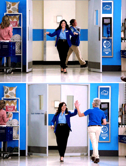 Amy walking through double doors and high-fiving an employee
