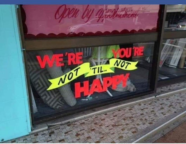 a shop's sign that strangely reads we're you're not til not happy