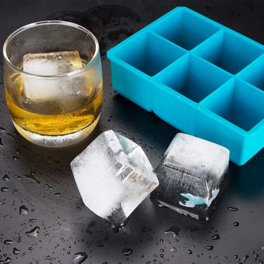 The ice cube tray next to two cubes and a cocktail
