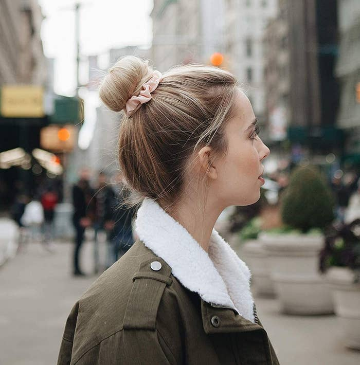A person using a sating scrunchie to hold their bun in place