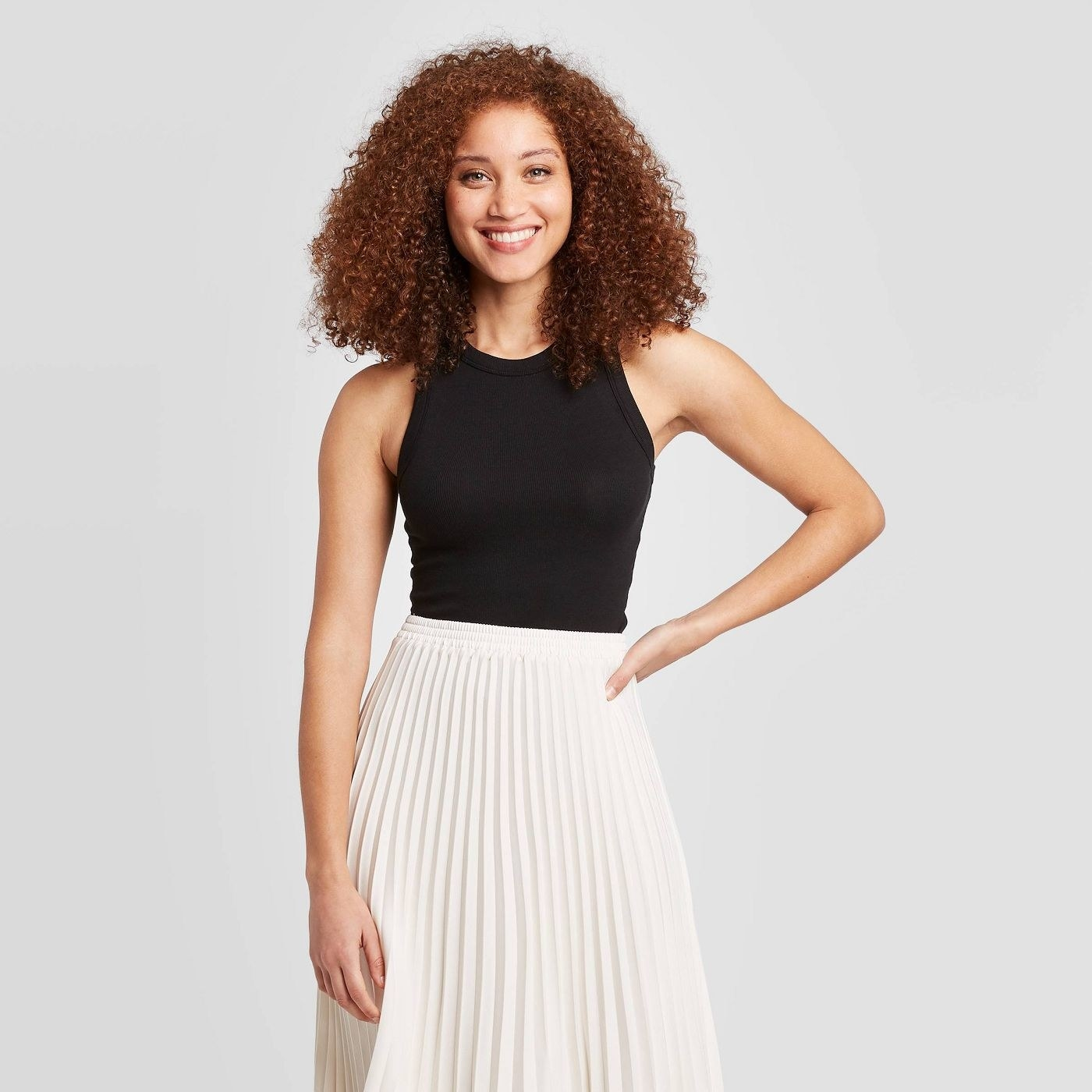 Model in black tank top and white skirt