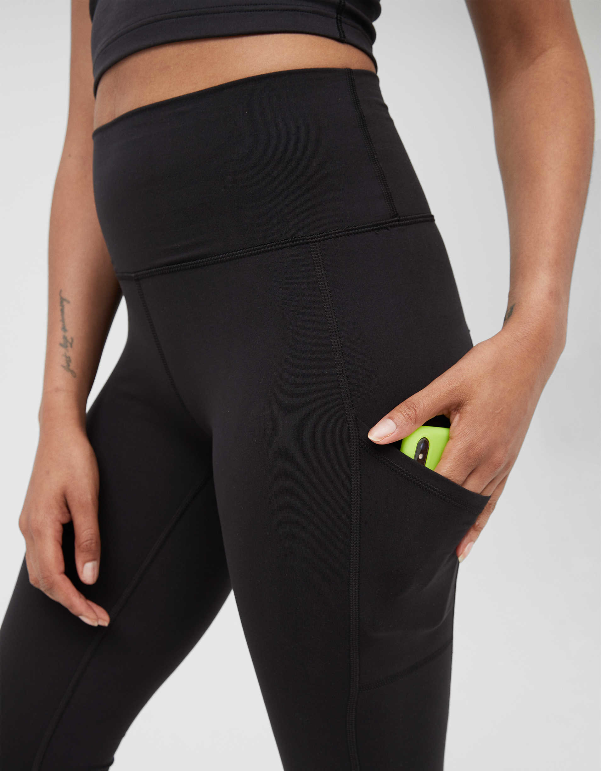 Closeup of a model wearing the black leggings with a hand on a phone in the side pocket
