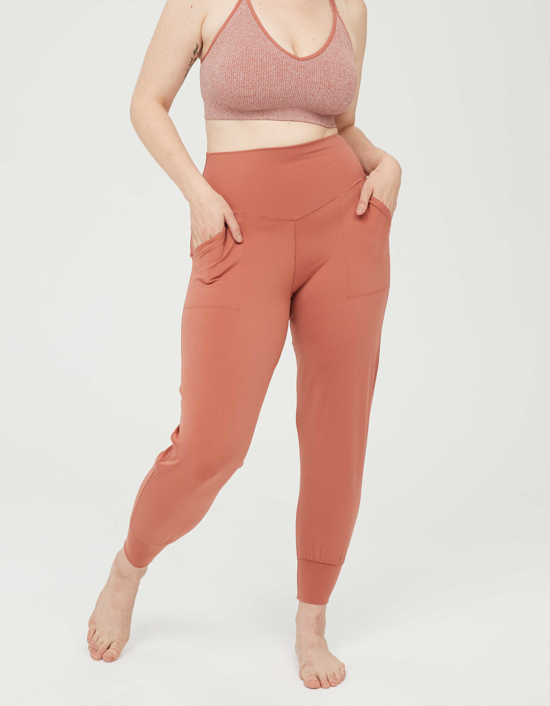 Model wearing the high-waisted joggers with cuffs and two front pockets in orange