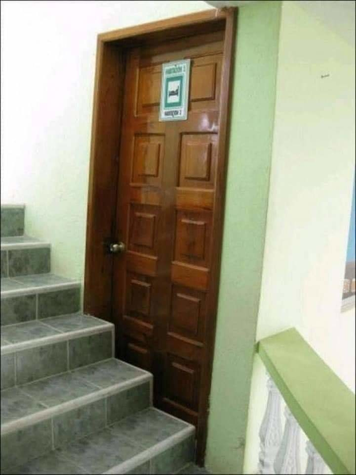 a door that strangely is blocked by a staircase