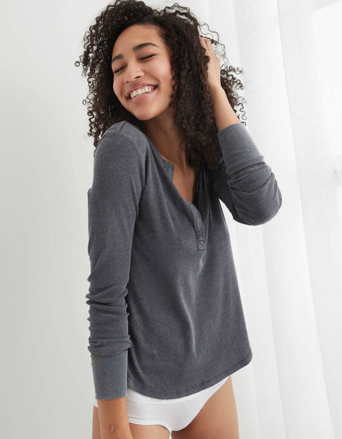 Model wearing the long-sleeved shirt in dark grey with snap buttons a quarter of the way down