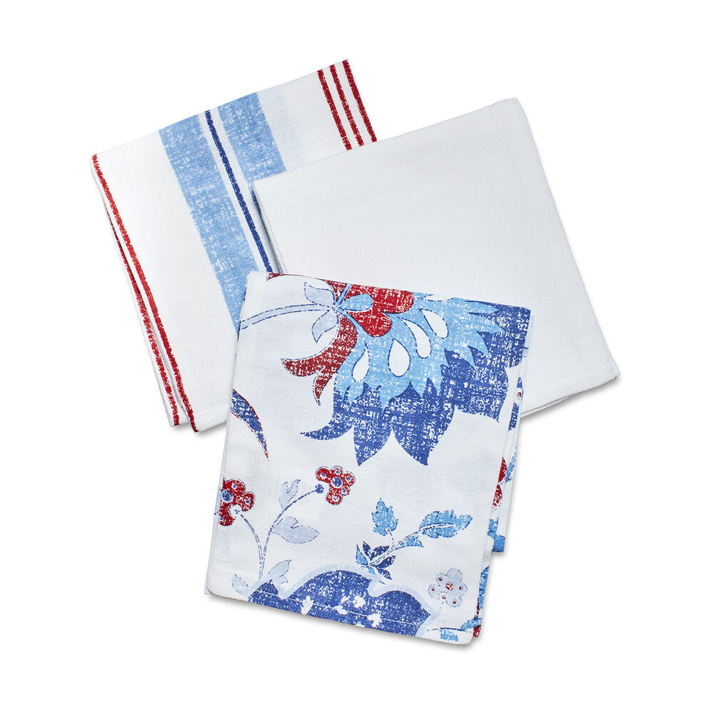 Three folded towels — one is plain white, one is white with blue and red flowers, and one is white with blue and red stripes