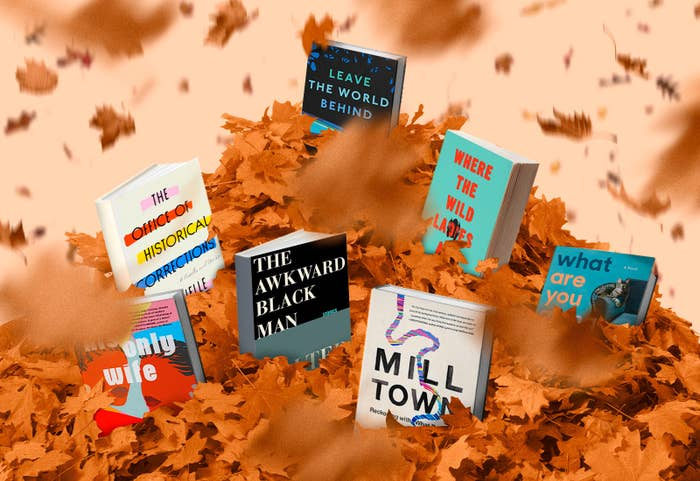 Several books in a large pile of fallen leaves.