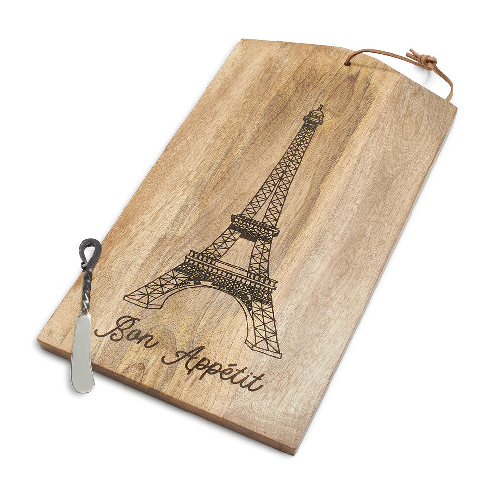 """The rectangular shaped board with an Eiffel Tower design and the phrase """"Bon Appetit"""" on it and a small cheese spreader"""