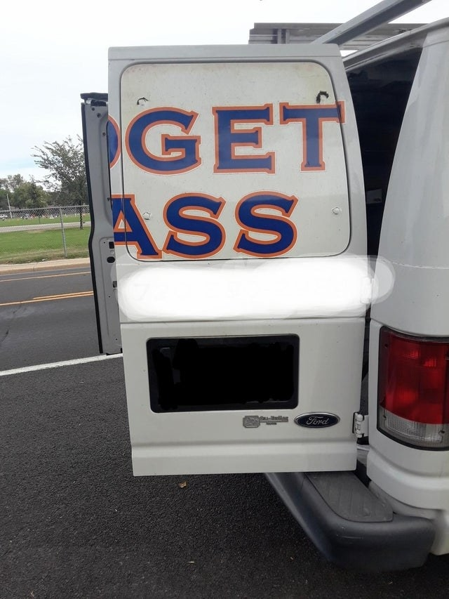 a van has its doors open and the text on one of the doors unfortunately reads get ass