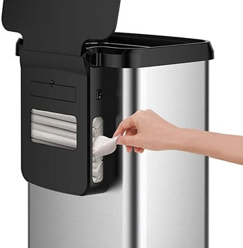 The back of the GLAD Extra Capacity Stainless Steel Sensor Trash Can where a model pulls a garbage bag out of the rear holder