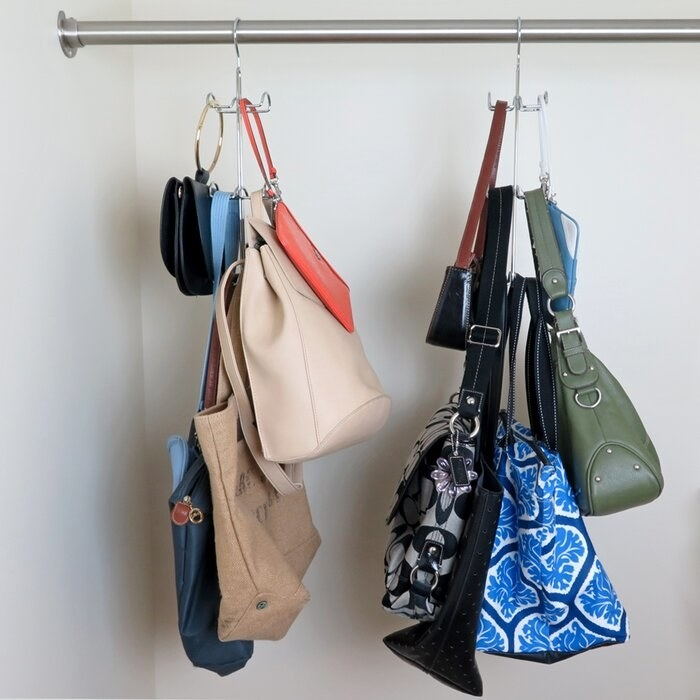 Two of the handbag hooks on a closet rod each holding various handbags of different sizes