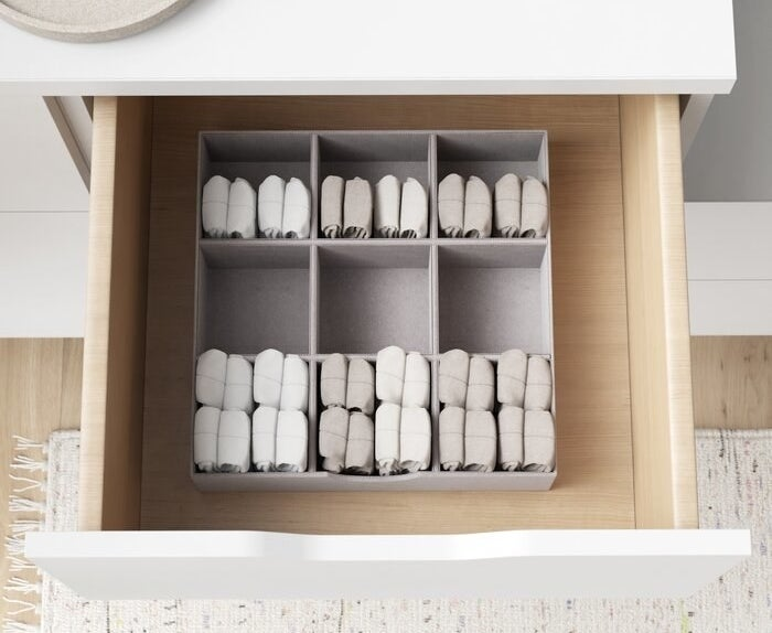 The gray organizer inside of a drawer with folded garments inside of it