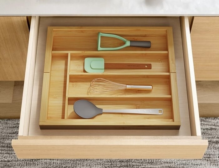 The wooden organizer inside of a drawer holding utensils like a spatula, a whisk, and a spoon