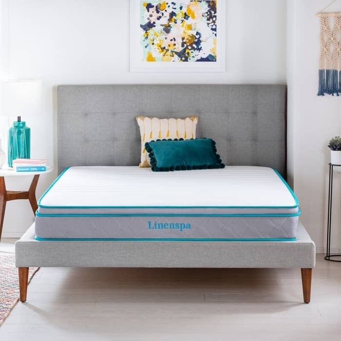 A light gray mattress with teal-colored piping and logo