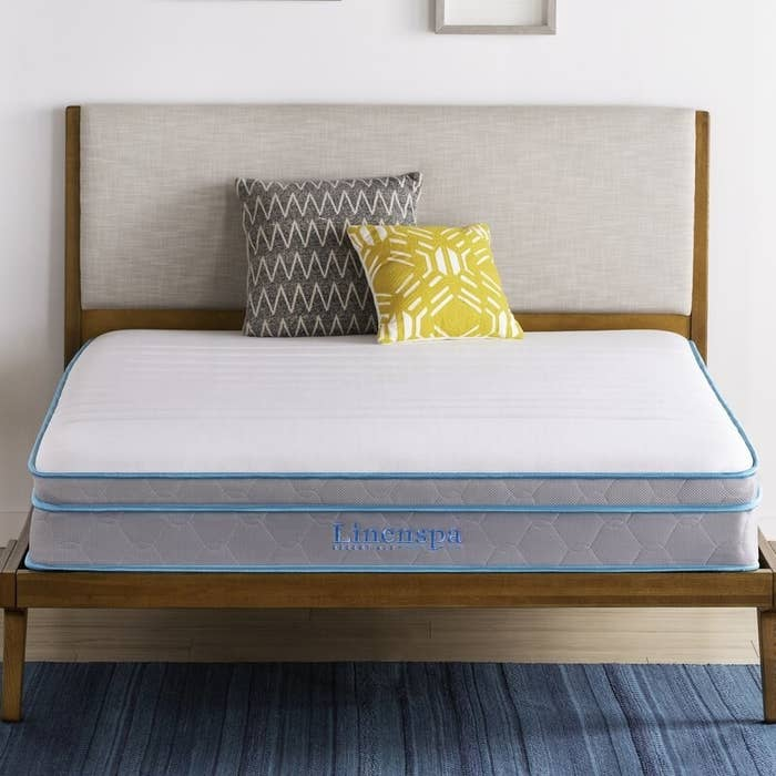 Light gray quilted mattress with light blue piping and logo
