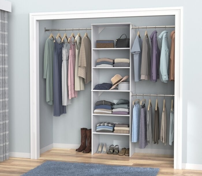 The closet system featuring three hanging rods, and a tiered shelf