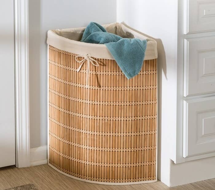 The tan colored wicker hamper against the corner of a wall filled with laundry