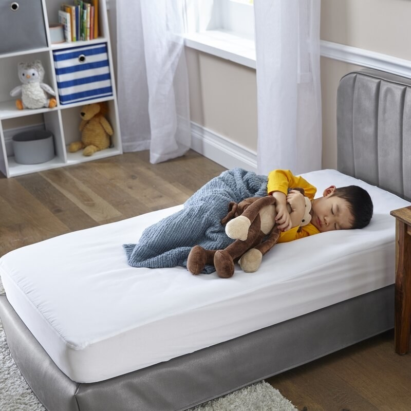 A toddler sleeping on a white mattress