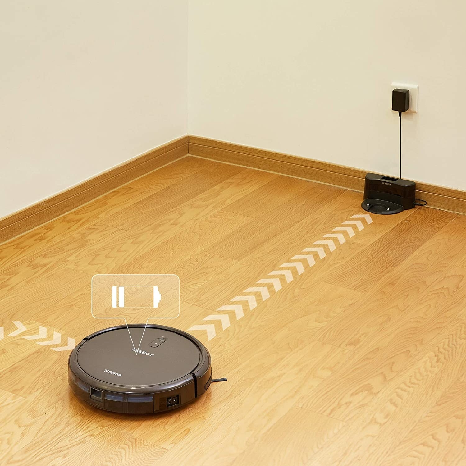 The robot vacuum returning to its base, which is plugged into an outlet