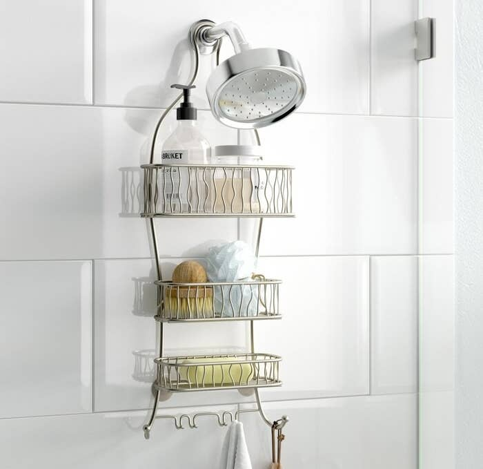 The silver shower caddy hanging over the shower head holding various shower products