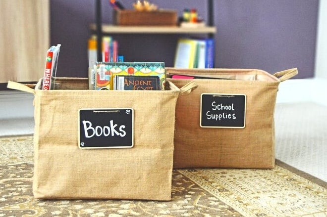 Two of the bins — one is labeled as books and is holding books, and the other is labeled as school supplies