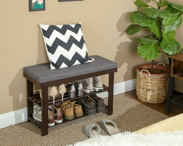 A shoe rack storage bench with six pairs of shoes being stored on it (three on each tier)