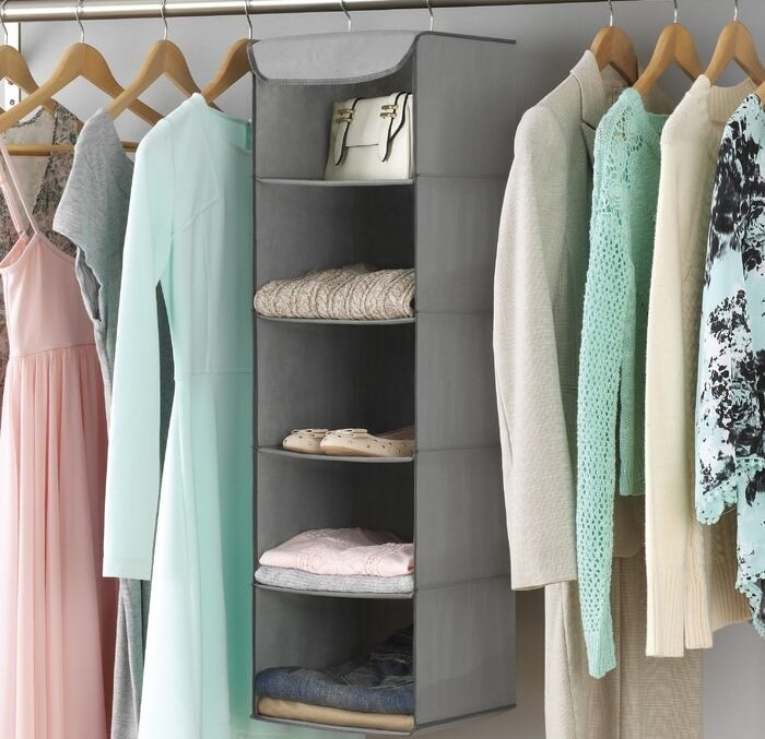 The gray tiered organizer hanging in a closet holding folded pants, folded sweaters, a pair of shoes, and a handbag