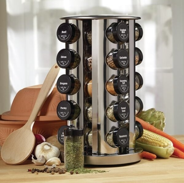 The spice rack filled with the various spices — the lids for each one are labeled with the name of the spice that's inside of it