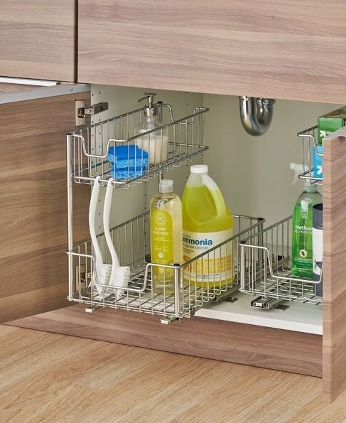 The under-the-sink pull-out organizer holding various cleaning products, sponges, scrub brushes, and plastic bag boxes