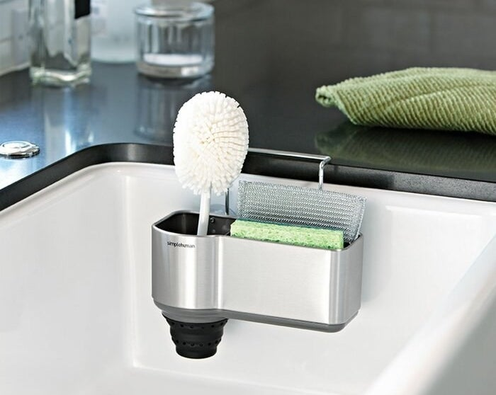 A shower caddy attached to a sink holding a sponge and a scrubbing brush