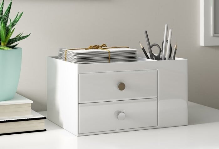 The organizer in white — there are two drawers, a storage cup area filled with pens, pencils, and a scissor, and an additional storage space at the top where a stack of papers are sitting