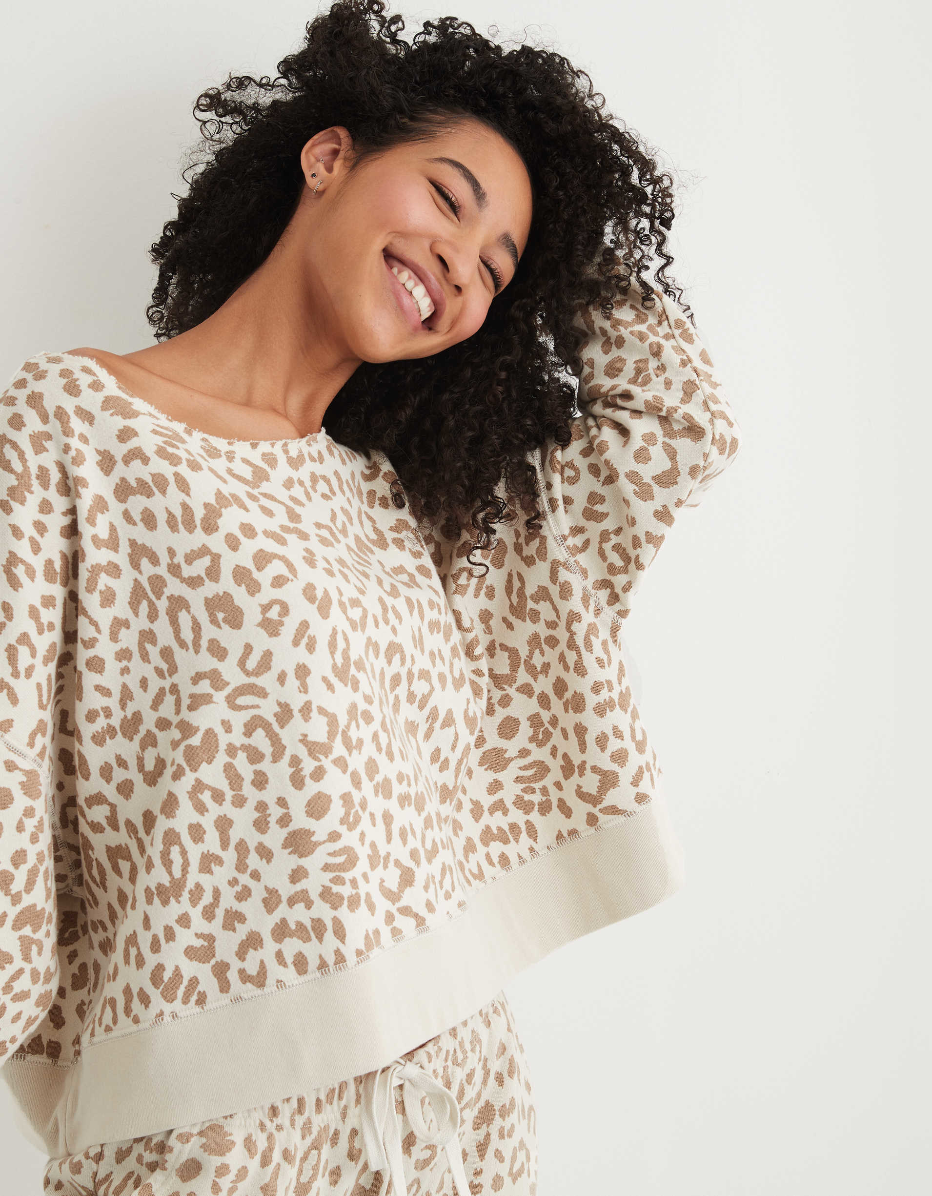 Model wearing the sweatshirt in cream with brown leopard print and a wide scoop neck
