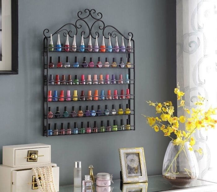The organizer hanging on a wall holding numerous colors of nail polish
