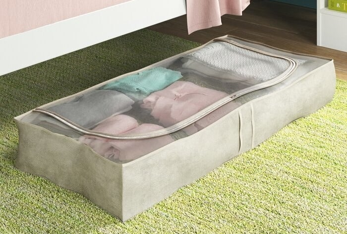 The storage bags organizer pulled out from underneath a bed with folded clothing inside