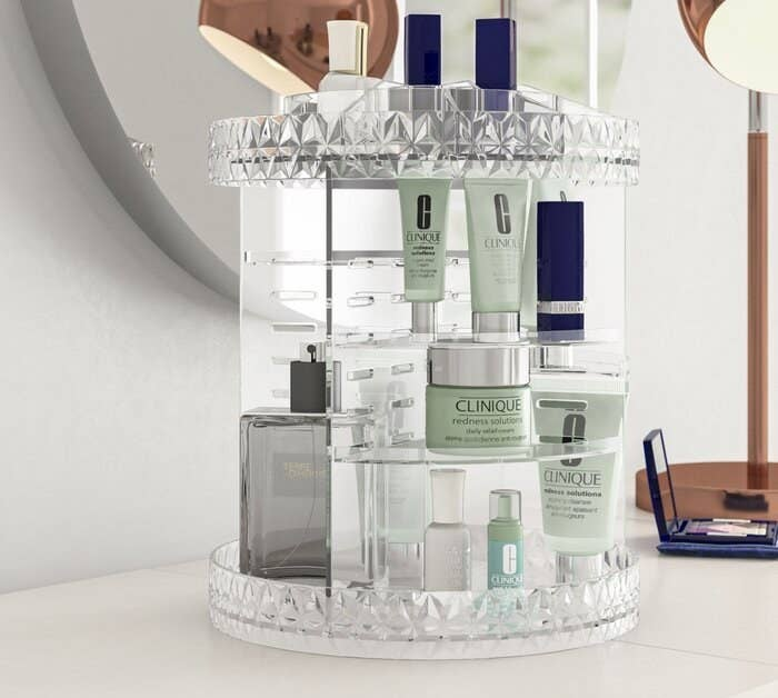 The rotating organizer in clear holding various makeup and skincare products, as well as perfumes