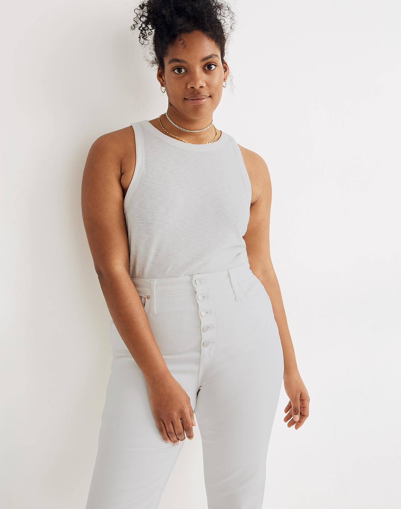 model wearing white high neck tank with white jeans
