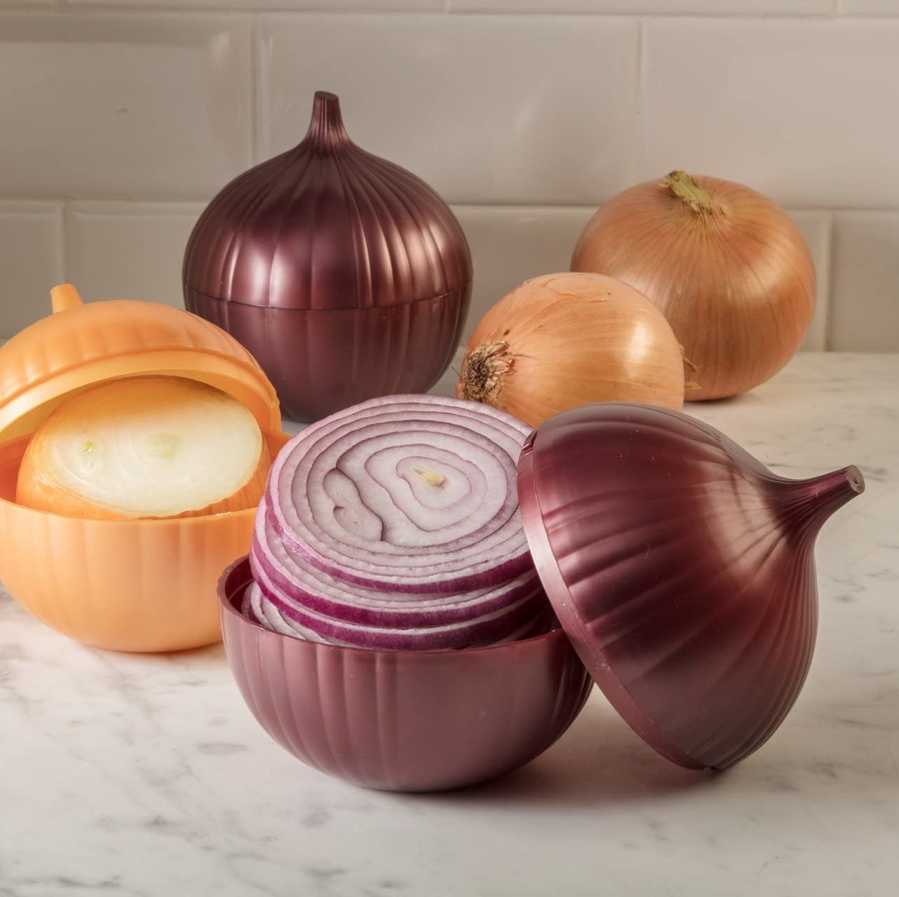 The onion saver tipped open on a counter to show the red onion inside