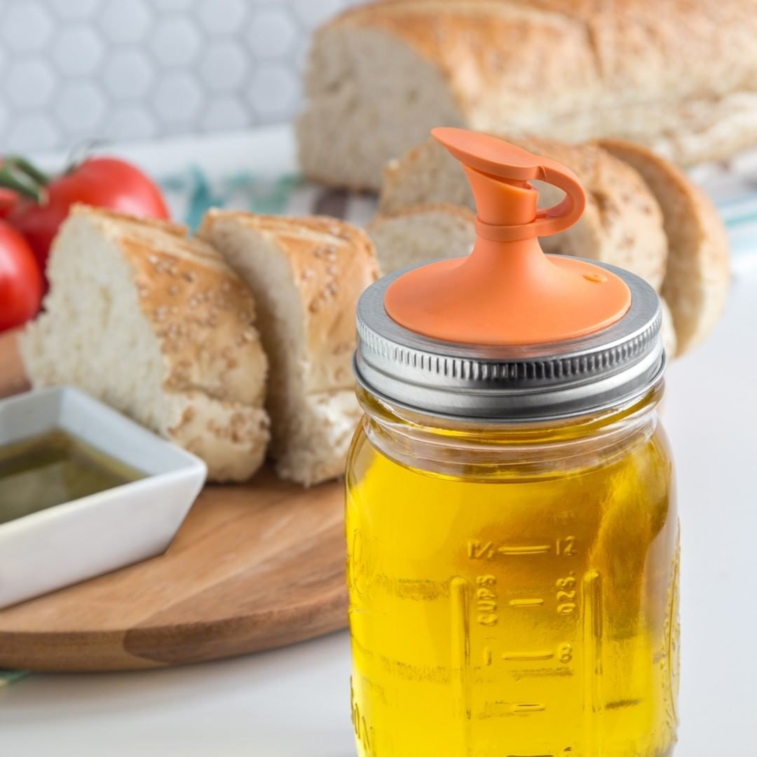 A close up of the spout and lid attached to a Mason jar full of oil