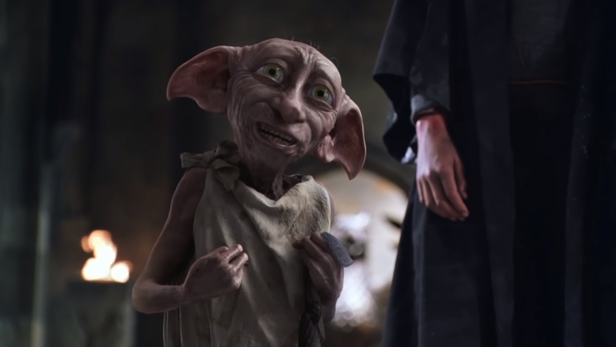 Dobby by Lucius Malfoy's side looking at Harry Potter with a lot of love