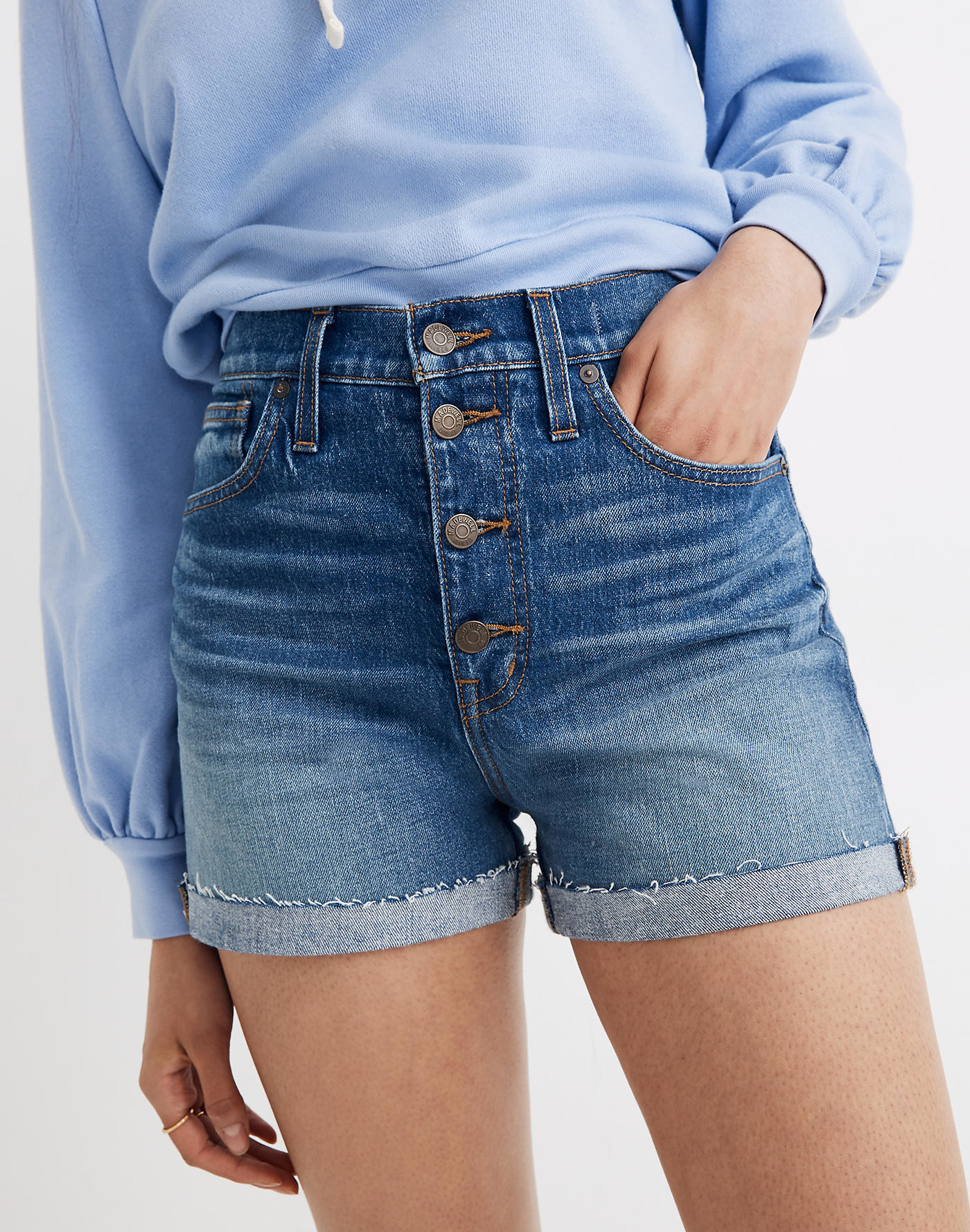 model wearing blue denim shorts with a four button closure