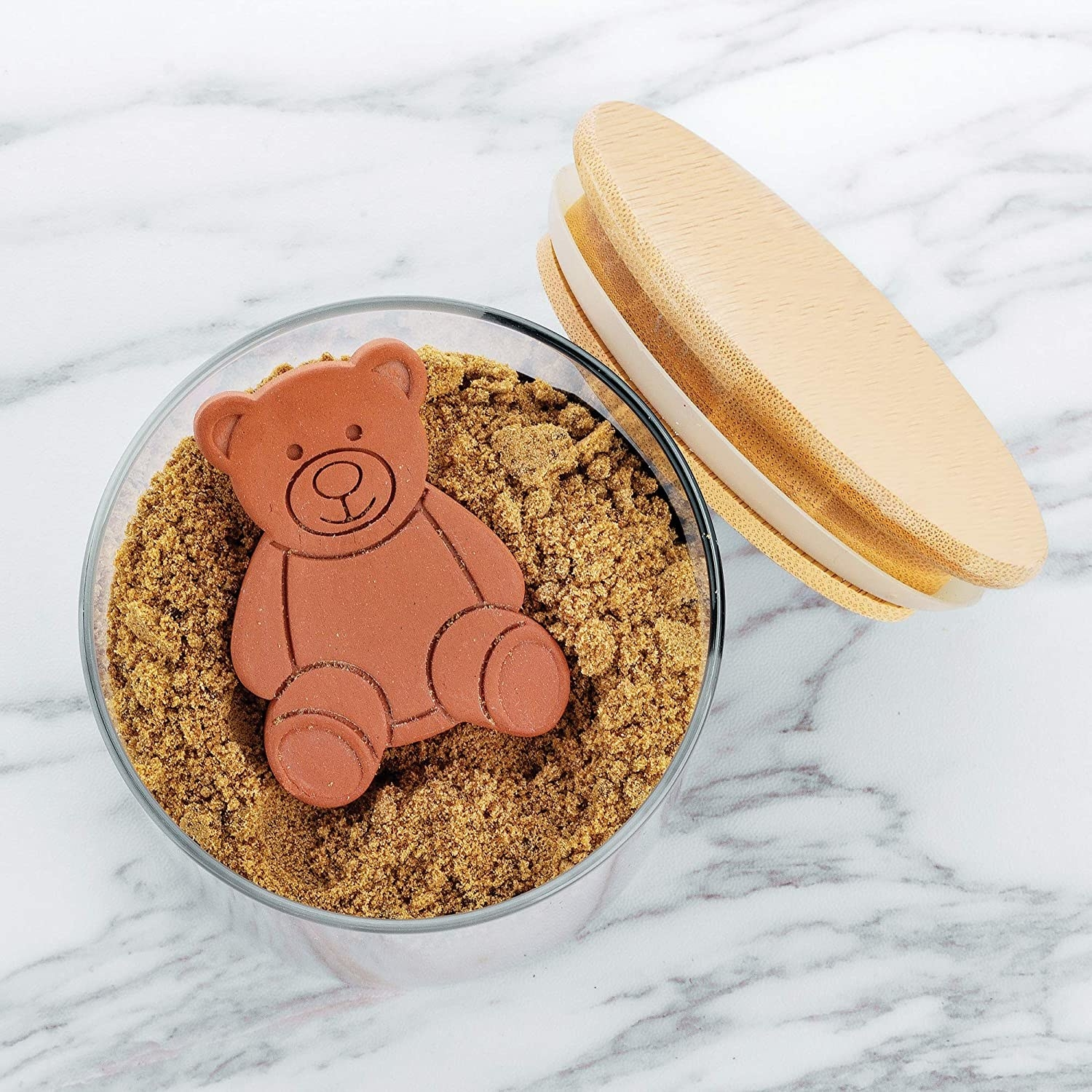 A flatlay of the teddy bear shaped saver inside a jar of brown sugar