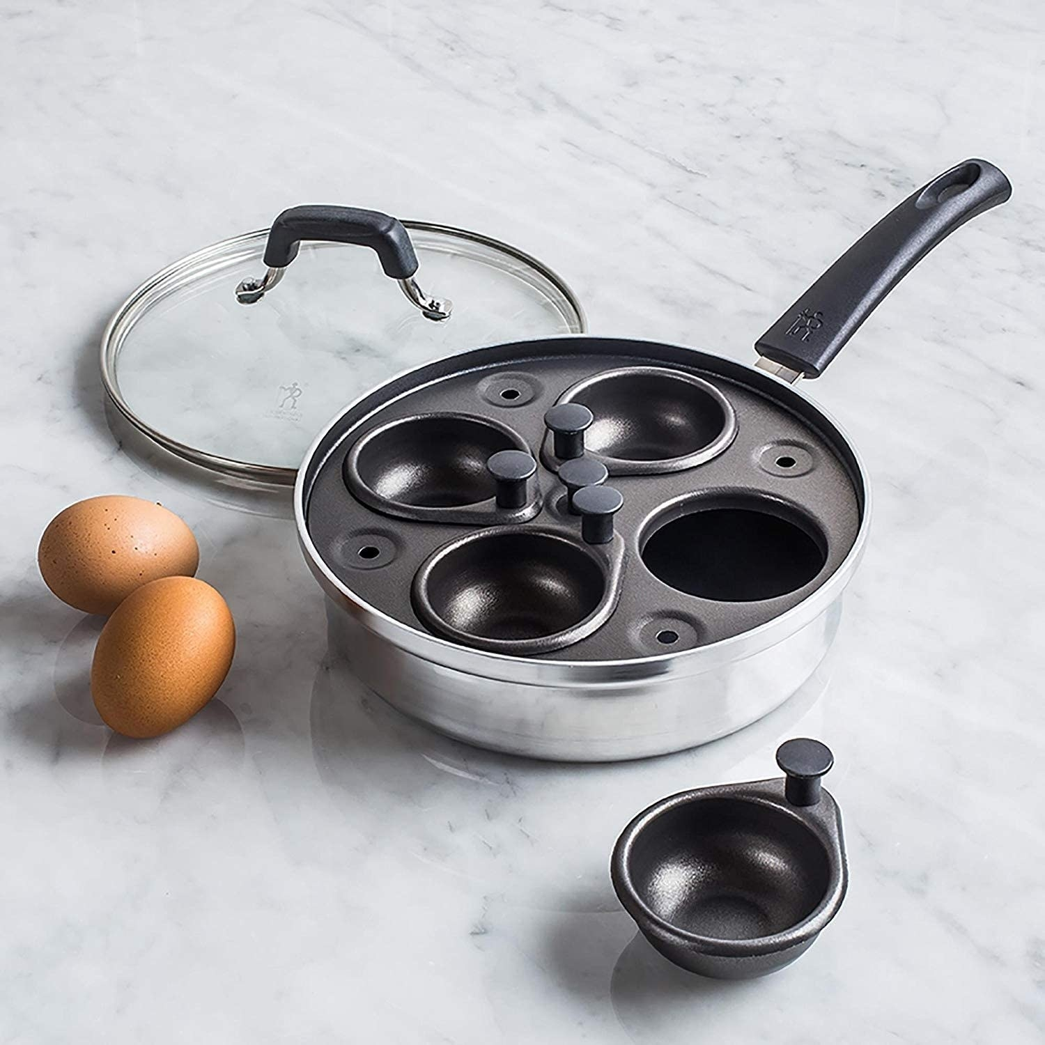 The egg poacher pan on a marble countertop with one of the pockets removed