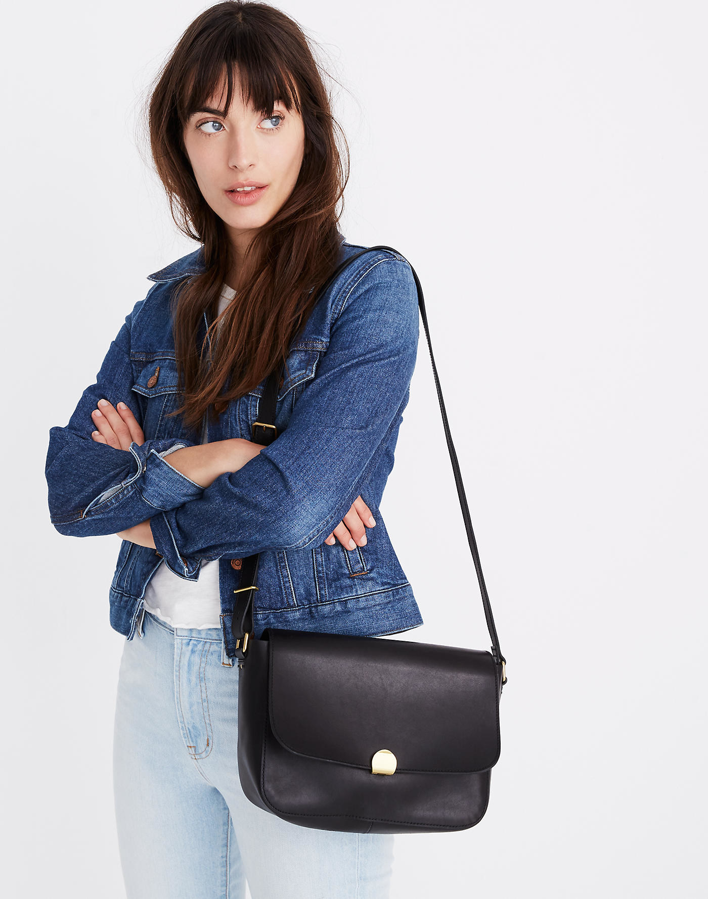 model carrying black crossbody purse
